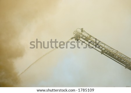 Firefighters' tools,  hose and ladder in action on burning building in Quebec, Canada - stock photo
