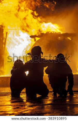 Firefighters watching a fire burn - stock photo