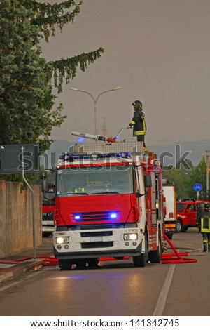 firefighters with the fire truck when switching off a fire in a factory - stock photo