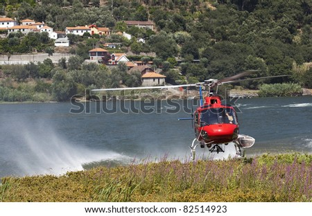 Firefighting helicopter on a collecting water in the river - stock photo