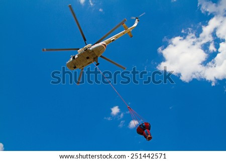 Firefighting helicopter with fire bucket flies against a clear blue sky - stock photo