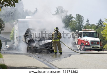 fireman and vehicle fire. - stock photo