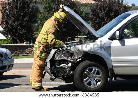 Fireman checking crashed car - stock photo