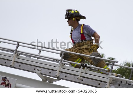 fireman climbing a ladder to enter a building - stock photo