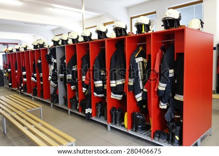 Fireman coats, helmets and boots wait for the next call. Dressing room of the volunteer fire department - stock photo