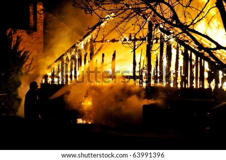 Fireman direct water stream on the burning house - stock photo