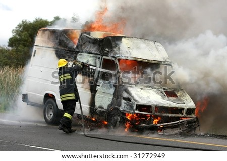Fireman extinguishing a fire in a burning delivery van - stock photo