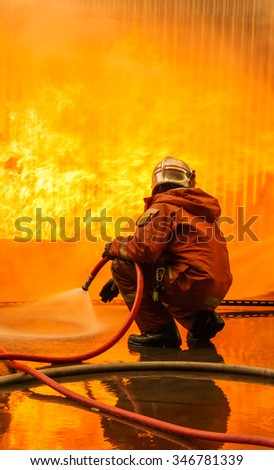 Fireman fighting a burning flames, try to fight flames of fire - stock photo