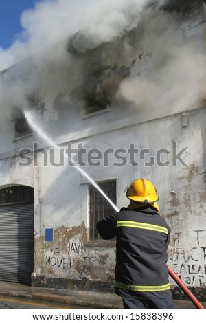 Fireman fighting a fire in a burning building with a water hose - stock photo