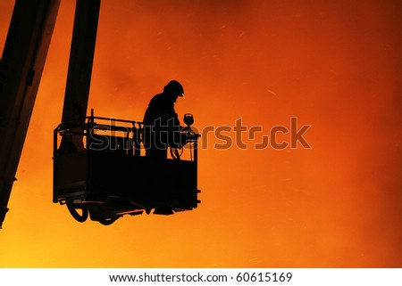 Fireman fighting a large fire - stock photo