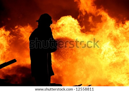 Fireman fighting a raging fire with huge flames of burning timber - stock photo