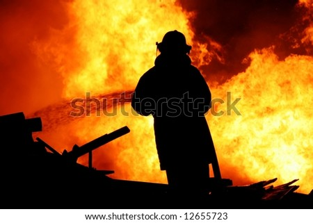 Fireman fighting a raging fire with huge flames of burning timber