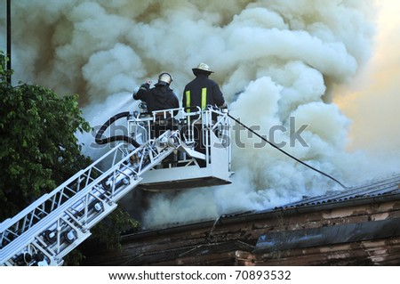 Fireman fighting against fire with a water cannon - stock photo