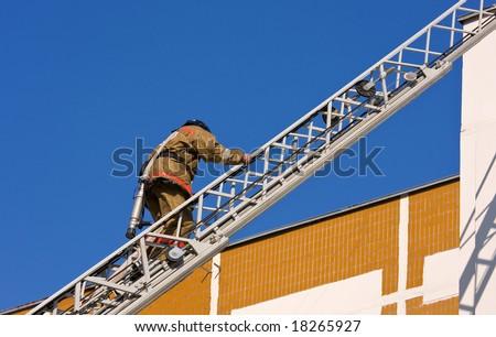 Fireman goes upward on a ladder - stock photo