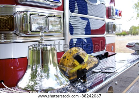 fireman helmet on the front bumper of a fire engine - stock photo