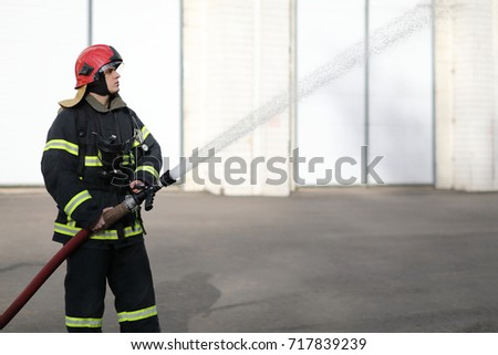 fireman holds and adjust nozzle and fire hose spraying high pressure water
