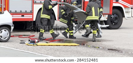 fireman in action during a road accident with car parts and the firetruck