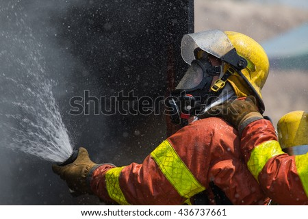 fireman in helmet and oxygen mask  spraying water to fire surround with smoke and drizzle - stock photo