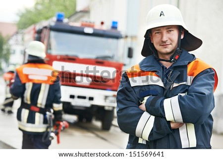 Fireman in uniform in front of fire engine or fire truck during training - stock photo