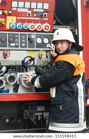 Fireman in uniform operating fire engine or fire truck on duty during training - stock photo
