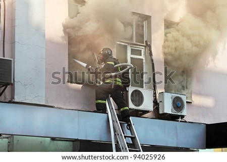 Fireman on the ladder extinguish the fire through the window of a burning house - stock photo