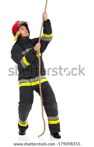 Fireman pulling a rope and looking up. Full length studio shot isolated on white. - stock photo
