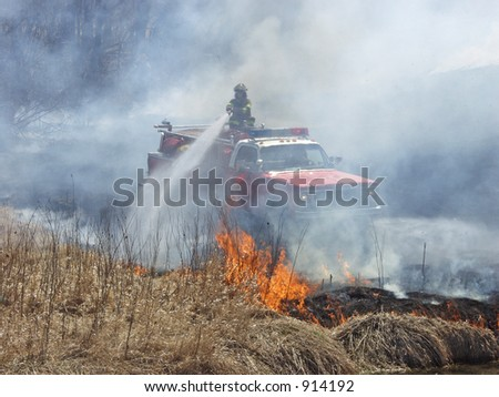 Fireman putting out brush fire - stock photo