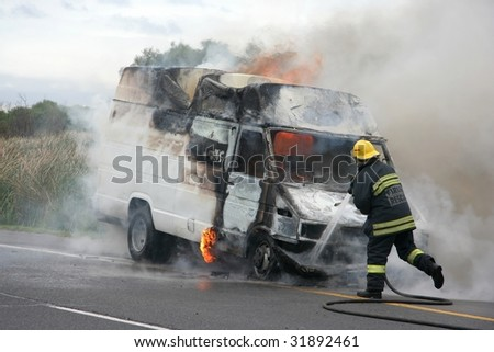 Fireman running to put out burning truck - stock photo