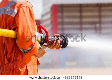 Fireman showing how to use a fire sprinklers. on a training fire - stock photo