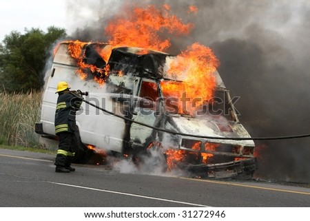 Fireman spraying water into a burning van on a road - stock photo