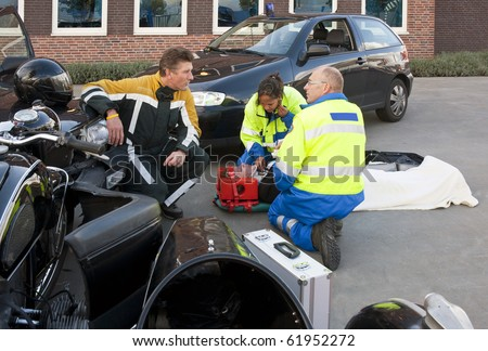 Fireman talking to a paramedic at the site of an accident, whilst a female paramedic checks up on the victim on a stretcher - stock photo
