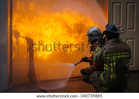 fireman training and fighting a flames of burning fire