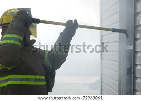 fireman using pike pole - stock photo