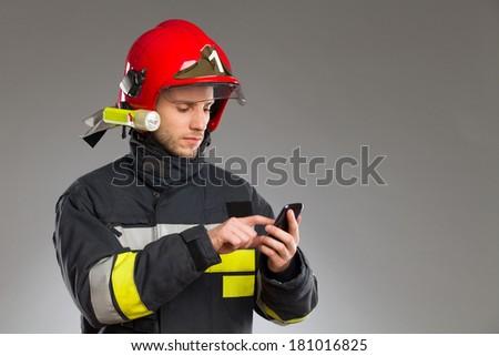 Fireman using smart phone. Waist up studio shot isolated on white. - stock photo
