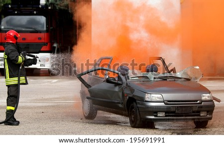 Fireman while off a fire of a car set on fire - stock photo