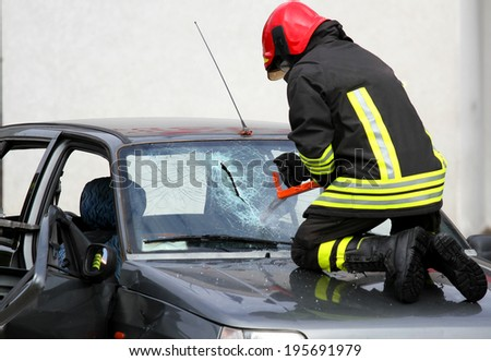 Fireman with protective overalls and work gloves while breaking a car windshield - stock photo