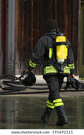 Fireman with the oxygen cylinder after turning off the fire home - stock photo