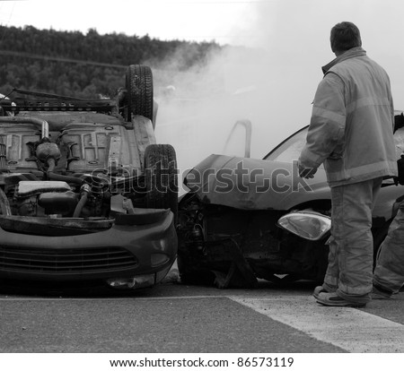 Firemen  at the scene of a serious car accident on a dark, rainy fall day, desaturated.  Part of a series. - stock photo
