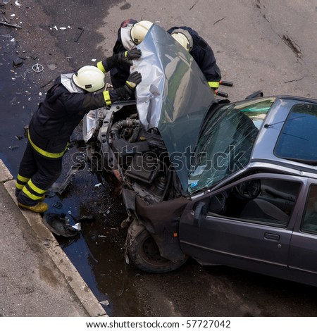 Firemen at traffic accident site, checking car, holding engine hood open - stock photo