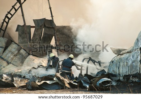 Firemen attending the scene of a fatal airplane crash with thick gray acrid smoke. - stock photo