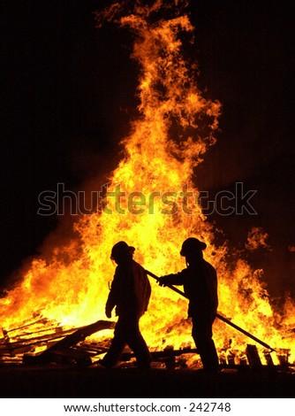 Firemen control a bonfire. - stock photo