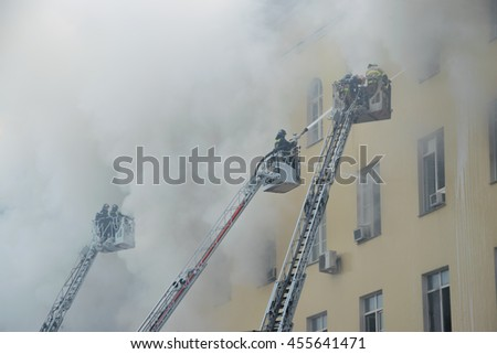 Firemen extinguish fire on fire trucks ladders - yellow building in smoke - stock photo