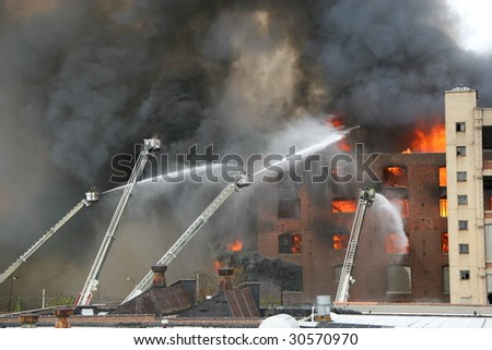Firemen extinguishing a raging fire - stock photo