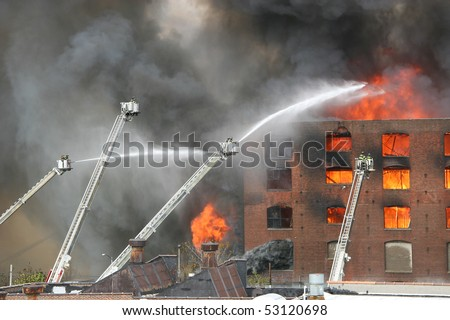 Firemen extinguishing a raging fire - stock photo