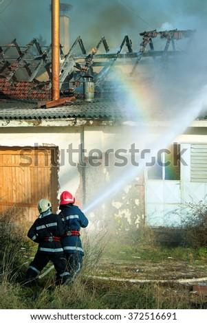 Firemen extinguishing fire - stock photo
