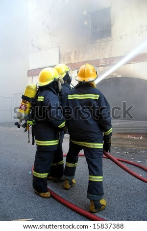 Firemen fighting a fire in a burning building with a water hose