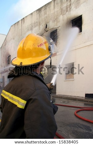 Firemen fighting a fire in a burning building with a water hose - stock photo