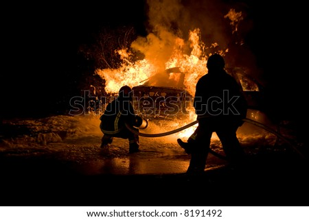 Firemen fighting a flaming car after an explosion - stock photo