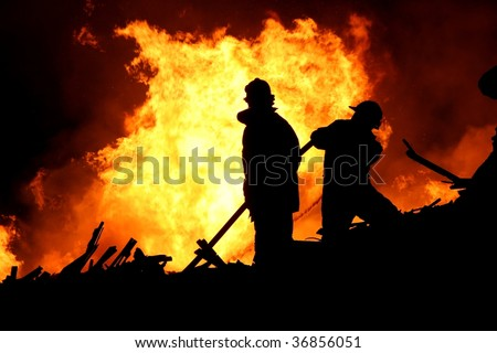 Firemen fighting a raging fire with huge flames of burning timber