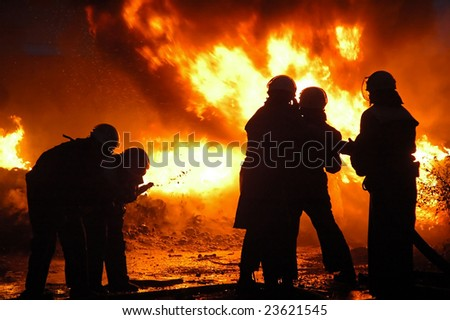 Firemen in a uniform liquidate a heavy fire.